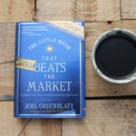 my copy of the little book that still beats the market, cup of coffee