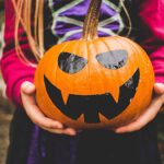 child in halloween costume holding pumpkin decorated for Halloween