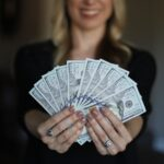 woman holding $1,000